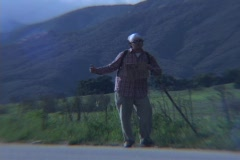 A hiker attempts to hitch a ride in a rural area during golden-hour. Stock Footage
