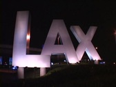 Spotlights illuminate the giant letters LAX at the entrance of Los Angeles Stock Footage