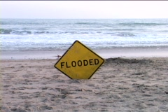 A street sign that reads FLOODED is stuck in the sand on a dry part of a beach Stock Footage