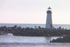 Medium shot of a lighthouse with people observing the water and a gull swooping Stock Footage