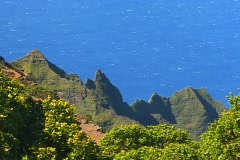 A trail cuts through lush vegetation and triangular volcanic rocks whose Stock Footage