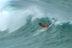 Kneeling on his board, surfer stands to catch a breaking wave and briefly rides Stock Footage