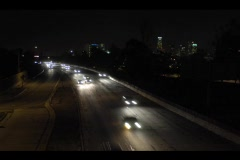Traffic speeds along a busy freeway at night in this accelerated shot. Stock Footage