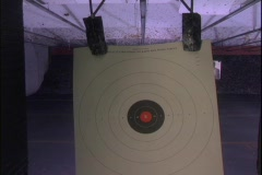 A target at an indoor shooting range recedes toward a far wall. Stock Footage