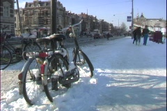 Bicycles sit in the snow on an Amsterdam street. Stock Footage
