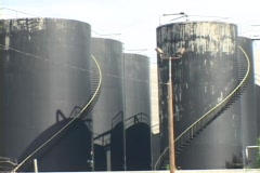 The camera pans across rows of large black industrial storage tanks. Stock Footage