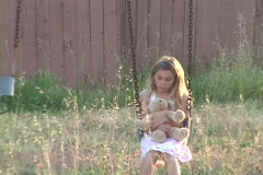 The camera zooms-out from a sad little girl holding a teddy bear on a swing to a - stock footage