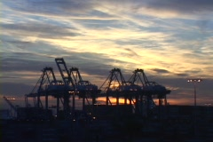 Medium shot of clouds flowing past  shipping cranes in a large port. Stock Footage