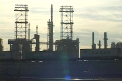 Medium shot of train traveling beside an oil refinery. Stock Footage