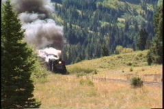Pan-right shot of a steam freight train chug through the Colorado mountains. - stock footage