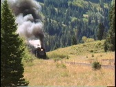 Pan-right shot of a steam freight train chug through the Colorado mountains. Stock Footage