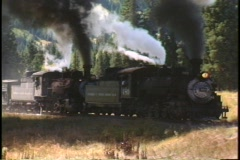 Tracking-right shot of two steam engines pulling a freight train  - stock footage