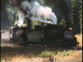 Tracking-right shot of two steam engines pulling a freight train  Stock Footage