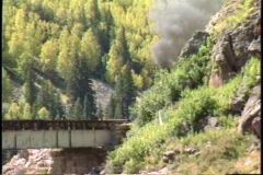 Following shot of a steam freight train crossing a bridge in the Colorado Stock Footage