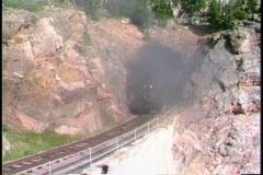 Pan-left shot of a Rio Grande steam freight train chug  through a tunnel in a - stock footage
