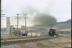 Pan-left shot of a Union Pacific steam train passing by grain silos in a small Stock Footage