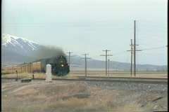 Pan-right shot of a fast moving steam passenger train. Stock Footage