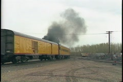 Medium shot of a steam train disappearing down the tracks. Stock Footage