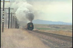 Tracking-right shot of a steam passenger train racing down the tracks. Stock Footage