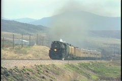 Tracking-left shot of a steam train speeding down the tracks. Stock Footage