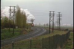Following shot of a steam passenger train rounding a bend. Stock Footage