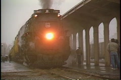 Pan-left shot of a steam passenger train at a station on a rainy day. Stock Footage