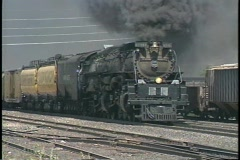 Tracking shot of a steam train passing through a freight yard. Stock Footage