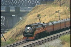 Zoom-out of a Southern Pacific train passing by a large highway bridge. Stock Footage