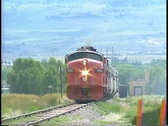 Pan-left shot of a diesel engine pulling a passenger train through the Stock Footage