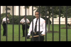Pan-right shot of a Latino security guard with a bat behind the White House Stock Footage