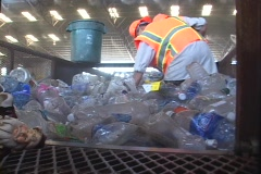 Workers at a recycling center sweep up plastic bottles. Stock Footage