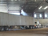 A tractor dumps debris into a container at a recycling center. Stock Footage