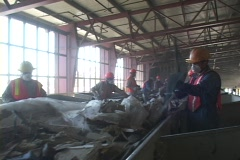 Workers at a recycling facility sort large objects from a - stock footage
