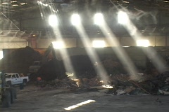 Bulldozers move recycling center materials through light beams. Stock Footage