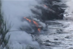 Ocean waves crash in on a lava flow on a Pacific Ocean island. - stock footage