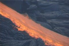 Red hot lava flows down a mountainside during a volcanic eruption. - stock footage