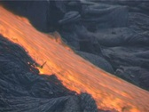 Stock Video Footage of Red hot lava flows down a mountainside during a volcanic eruption.