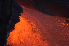 Red hot lava flows down the slopes of a volcano. - stock footage