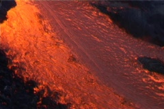 Red hot lava flows down a volcano  past blackened trees and - stock footage