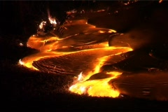 Hot molten lava slowly flows down a mountainside, through the - stock footage