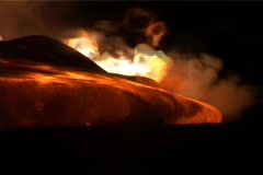 Flames erupt around a lava flow during a volcanic eruption. - stock footage