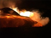 Flames erupt around a lava flow during a volcanic eruption. Stock Footage