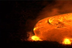 Molten lava  from a volcano slowly oozes, sending up smoke. - stock footage