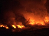 Clouds of flame, smoke, and steam  billow into the night sky Stock Footage