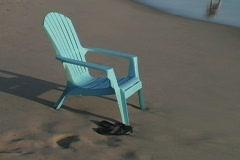 A deck chair sits on the beach as the waves roll in suggesting Stock Footage
