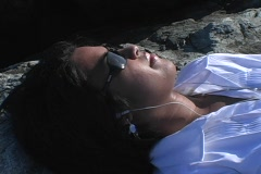 A woman with dark glasses lies in the sun listening to music Stock Footage