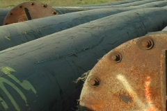 Pipes and metal fittings lie abandoned in a field. Stock Footage