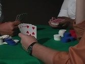 A dolly around a poker game reveals player's cards. Stock Footage