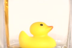 Oil fills up a clear container with a rubber duck floating on top. Stock Footage