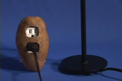 Tilt up from a potato to a light bulb which lights up, Stock Footage